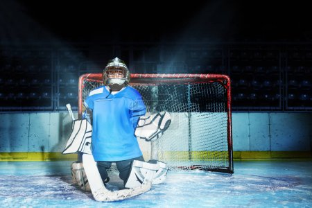 Portrait of young goaltender standing in kneeling position while guarding his net during hockey game