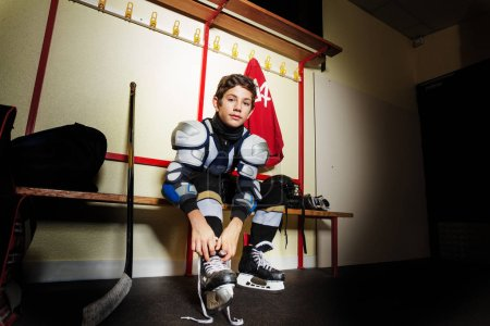 Photo for Portrait of teenage boy sits on the bench and ties hockey skates laces in dressing room - Royalty Free Image