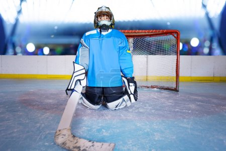 Young ice hockey goalie in kneeling position protecting the net