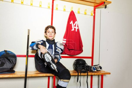 Photo for Portrait of teenage boy, professional hockey player, putting on ice skates in locker room - Royalty Free Image