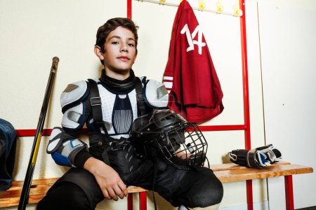 Photo for Close-up portrait of teenage boy in protective equipment sitting on the bench in men's ice hockey locker room - Royalty Free Image