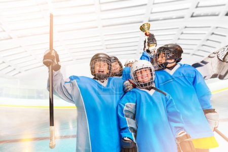 Portrait of excited boys, ice hockey players, holding the trophy above their heads and celebrating victory