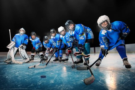 Children in blue uniform skating with the puck during hockey practice