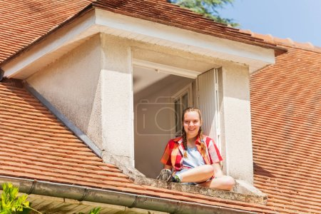 Low angle portrait of happy teenage girl sitting on the ledge of attic window and looking at camera