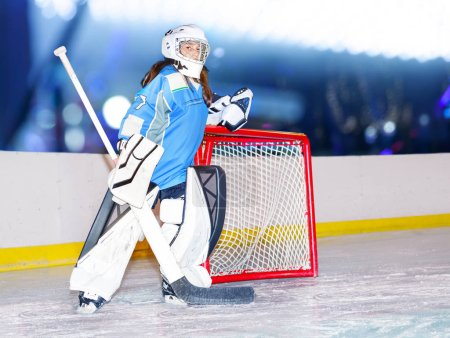 Photo for Portrait of teenage girl goaltender in protective equipment standing next to the net at hockey arena - Royalty Free Image