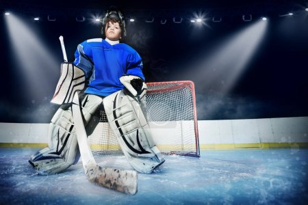 Photo for Low-angle portrait of young goalie, teenage boy in protective equipment, standing next to the net in the spotlight of ice hockey arena - Royalty Free Image