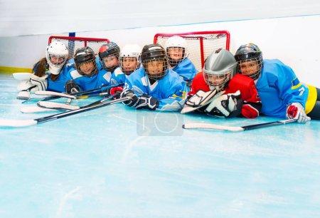 Foto de Los alegres niños y niñas puesta en pista del hockey sobre hielo después del partido - Imagen libre de derechos