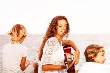 Photo pour Gros plan portrait de belle adolescente chantant avec guitare pour ses amis sur la plage - image libre de droit