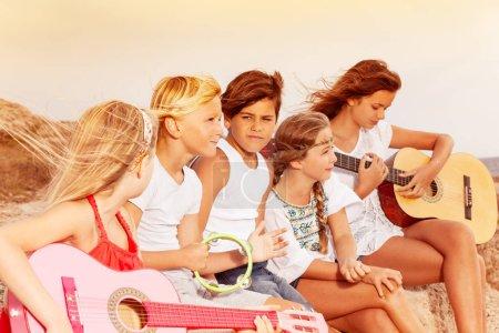 Photo pour Portrait d'adolescents, assis sur la plage, jouant de la guitare au coucher du soleil - image libre de droit