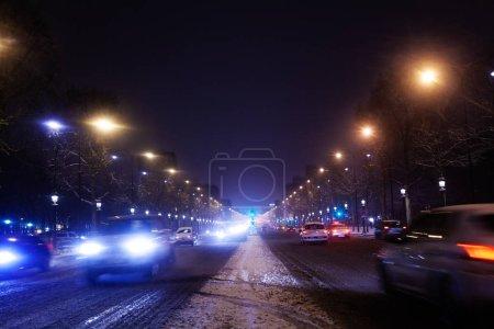 Photo pour Circulation sur l'avenue des Champs-Elysées la nuit enneigée, Paris, France - image libre de droit