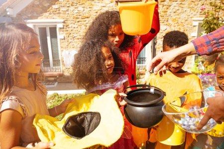 Photo pour Gros plan portrait de divers enfants à Halloween portant des costumes mignons recevoir des bonbons de l'adulte sur la pelouse en face de la maison - image libre de droit