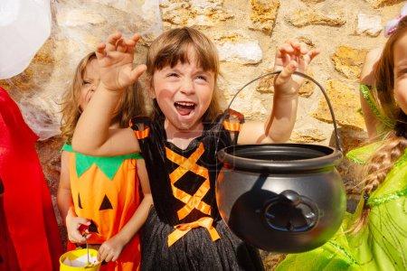 Photo pour Portrait d'une petite fille tenant seau pour bonbons debout dans un groupe d'amis avec geste effrayant sur le mur de pierre - image libre de droit