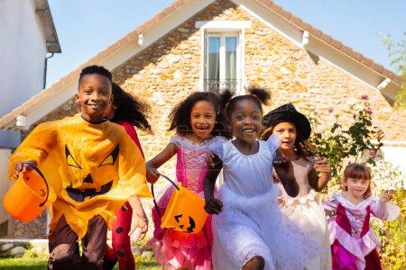 Photo pour Portrait rapproché d'un groupe d'enfants courir en costume d'Halloween sur la pelouse en face de la maison ensemble, criant avec des seaux de bonbons - image libre de droit