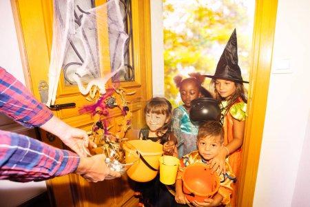 Photo pour Grand groupe d'enfants costumes d'Halloween debout dans la porte avec des seaux orange pour les bonbons reçoivent des bonbons de l'adulte - image libre de droit