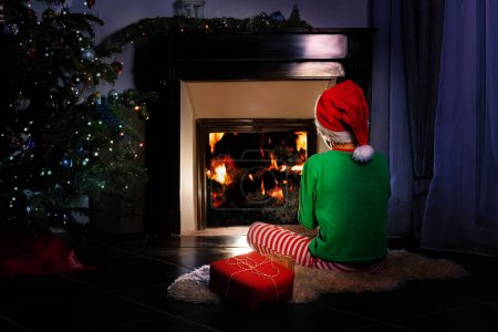 Photo for Boy from back with Christmas present in New Year costume sit near fireplace and looking on fire - Royalty Free Image