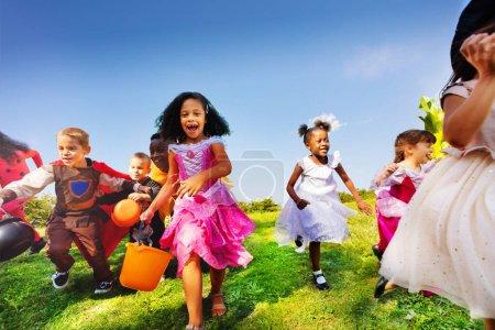Photo pour Grand groupe de petits enfants courir en costume d'Halloween sur la pelouse avec des seaux pour des bonbons - image libre de droit