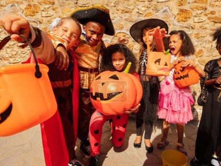 Photo pour Beaucoup d'enfants en costumes d'Halloween se tiennent ensemble tenant la citrouille dans un groupe d'amis avec des seaux pour des bonbons - image libre de droit