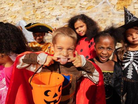 Photo pour Portrait du petit garçon sortir la langue et gesticuler en costumes d'Halloween - image libre de droit