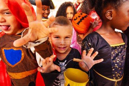 Photo pour Portrait rapproché du garçon sur un grand groupe d'enfants en costumes d'Halloween debout ensemble souriant montrant des gestes effrayants regardant la caméra - image libre de droit
