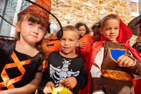 Photo pour Portrait d'un garçon dans le groupe de costume d'Halloween habillé enfants debout avec des seaux de bonbons - image libre de droit