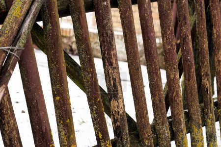 Photo for An old destroyed wooden fence in the countryside. Part of the fence is broken. Photo taken close up - Royalty Free Image