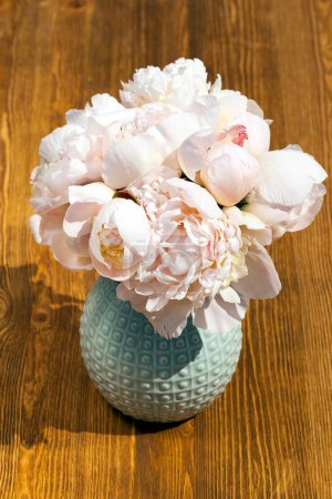 Photo for A few beige peony flowers put in a small vase standing on a wooden table. Spring season, close-up photo, top view - Royalty Free Image