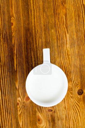 Photo pour Une tasse blanche de lait chaud debout sur une surface en bois. Photo gros plan, vue de dessus - image libre de droit