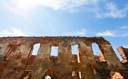 Photo for Part of the wall with windows of an ancient medieval building - Golshansky castle. Photo of a summer in a sunny day against a blue sky - Royalty Free Image