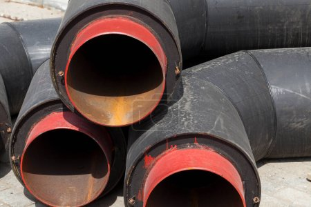 Photo for Large diameter wide metal pipes covered with a thick layer of black rubber. Close-up photo during sewer construction works - Royalty Free Image