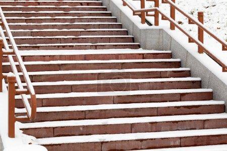 Photo pour Escalier couvert de neige dans le parc de la ville. L'escalier a une main courante. Étapes gros plan brun photographié d'en bas. - image libre de droit