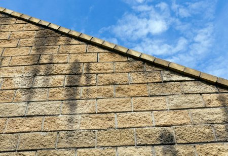 Photo for Part of a wall of large bricks against a blue sky. Details of the old structure - Royalty Free Image