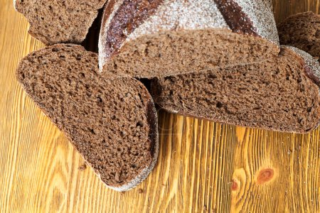 Photo for Pieces of rye bread on a wooden old table. Photo close up - Royalty Free Image