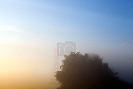 Photo for One metal high-voltage pole in the field. Summer landscape photo during the sunrise. part of the photo with the blue sky, and part of the yellow from the light of the sun at dawn. poor visibility due to haze - Royalty Free Image