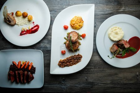 white plates with different dishes with meat, mashed potato, and wild rice on dark wooden table in restaurant