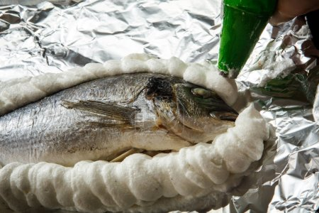 covering dorado stuffed with herbs on foil with whipped egg whites with salt