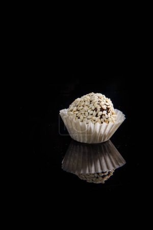 Photo for Closeup one healthy useful round organic handmade candy decorated with white sesame seeds on black mirror background - Royalty Free Image