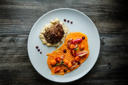 Photo for Top view tasty well-done meat steak on potato puree served with grilled vegetables on white plate on wooden table background - Royalty Free Image