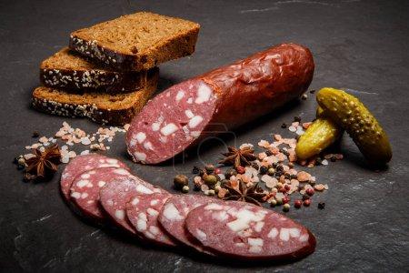 Photo pour Moitié de saucisse de salami fumée avec des morceaux tranchés servis avec du sel rose, des épices, des tranches de pain de seigle et des concombres marinés - image libre de droit