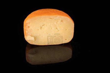 Photo pour Gros plan la moitié de la tête de fromage edam jaune dur avec des trous sur fond miroir noir avec réflexion et espace de copie - image libre de droit
