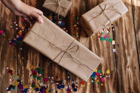 Photo pour Main femme ramasse un cadeau emballé dans du papier craft, qui se trouve sur une table en bois - image libre de droit