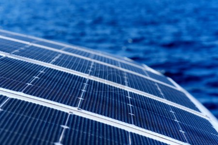 Photo for Close up view part of solar panel on dock of sailboat and blue sea waters during sunny day outdoors - Royalty Free Image