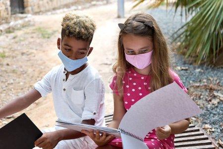 Photo pour Deux multi ethnique adorable 9s 10s ans fille et garçon assis sur le banc parler discuter de leurs dessins passer du temps libre ensemble en plein air. Loisirs, passe-temps et passe temps. Amitié égalité raciale concept d'amitié - image libre de droit