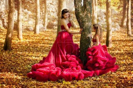 Photo pour Maman et sa fille dans des robes luxueuses dans la forêt d'automne - image libre de droit