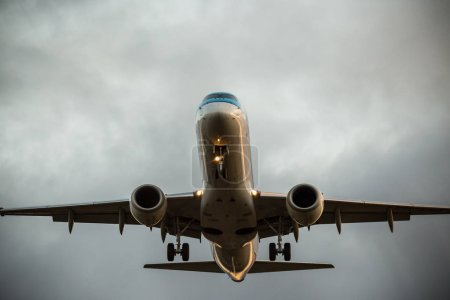 Commercial airplane flying under dramatic clouds.