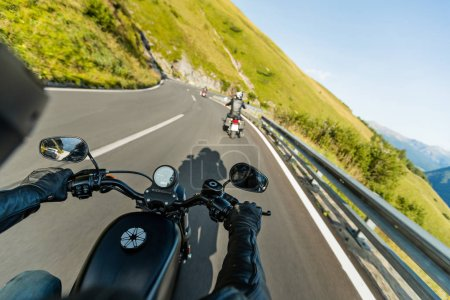 Motorcycle driver riding in Alpine highway, handlebars view, Austria, Europe.