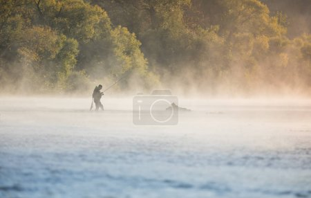 Man fishing in river with fly rod during summer morning.