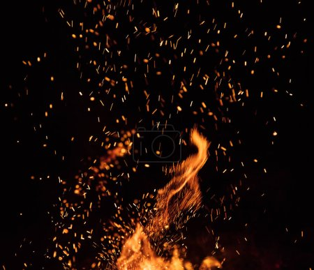 Photo for Burning sparks flying. Beautiful flames. Fiery orange glowing flying away particles on black background. - Royalty Free Image