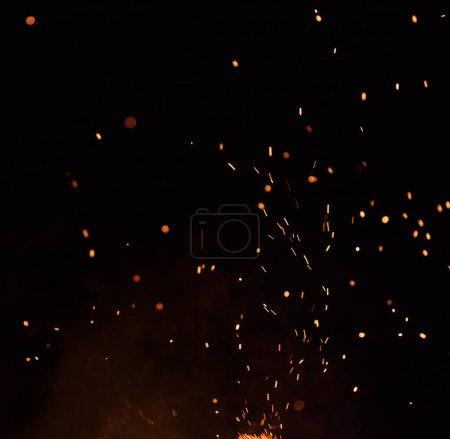 Photo pour Des étincelles brûlantes volent. De belles flammes. Orangé flamboyant s'envolant particules sur fond noir . - image libre de droit