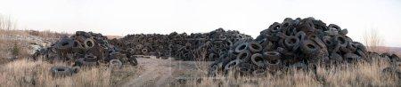 Photo pour Vieux pneus polluer la nature. Pollution de l'environnement. - image libre de droit