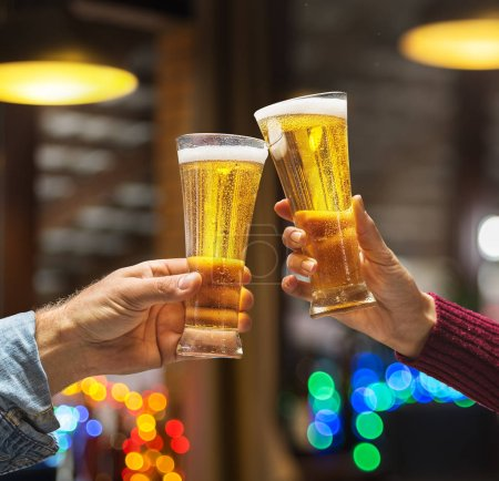 Beer glasses raised in a toast. Close-up hands with glasses. Blurred bar interior at the background.